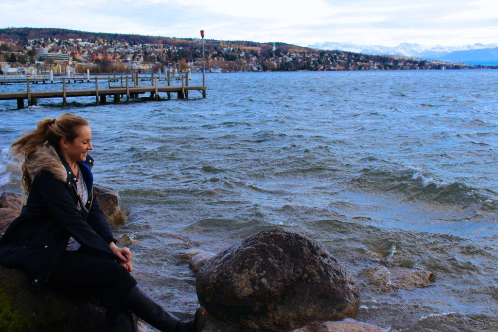 Maddy at the lake, sitting on a rock, while spending two days in zurich