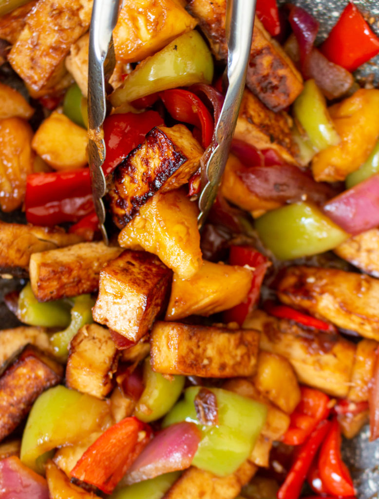 How to stir-fry sweet and sour tofu with pineapple. Sweet and Sour Tofu with Pineapple is a vegan version of the classic Chinese-American takeout dish. Marinated crispy tofu, sweet and juicy pineapple, red onion, and green and red bell peppers, all coated in a thick and delicious sweet and sour sauce, is perfect for a quick (35 minutes), super easy, and healthy weeknight meal. Serve it with rice, or even modify the recipe a bit and stir-fry some noodles with it, and you have an epic meal that everyone will love.