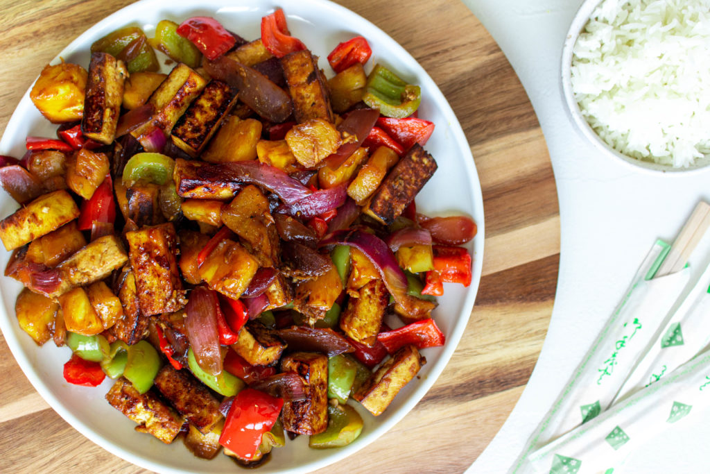 Sweet and Sour Tofu with Pineapple is a vegan version of the classic Chinese-American takeout dish. Marinated crispy tofu, sweet and juicy pineapple, red onion, and green and red bell peppers, all coated in a thick and delicious sweet and sour sauce, is perfect for a quick (35 minutes), super easy, and healthy weeknight meal. Serve it with rice, or even modify the recipe a bit and stir-fry some noodles with it, and you have an epic meal that everyone will love.