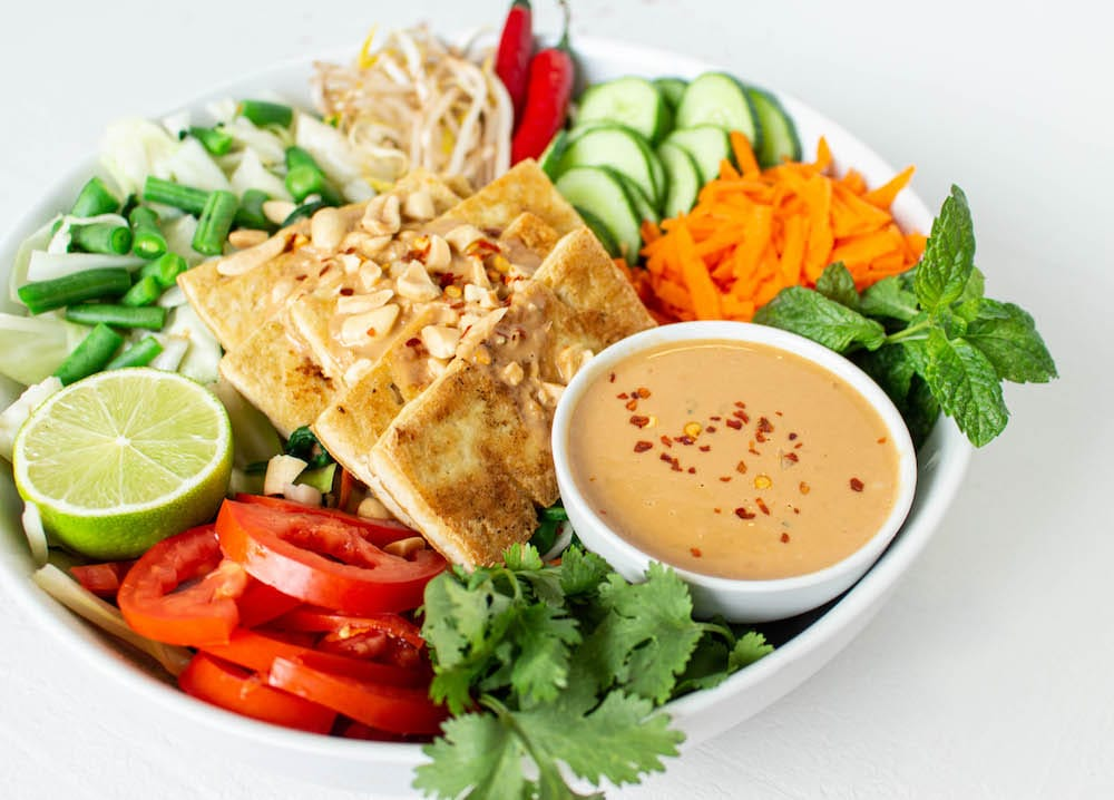 This recipe is my take on vegan gado gado salad, based on what I've learned over five trips to Bali and elsewhere in Indonesia, and multiple Indonesian food cooking classes while there. It is as traditional and authentic as possible, for being vegan. The recipe includes a delicious peanut sauce dressing, blanched vegetables, fresh veggies, lots of herbs, crispy tofu, and plenty of options for garnish, such as lime wedges, chili, fried shallots, peanuts, and rice crackers. This is the perfect option for a salad craving, quick (40 mins), easy, and delicious.