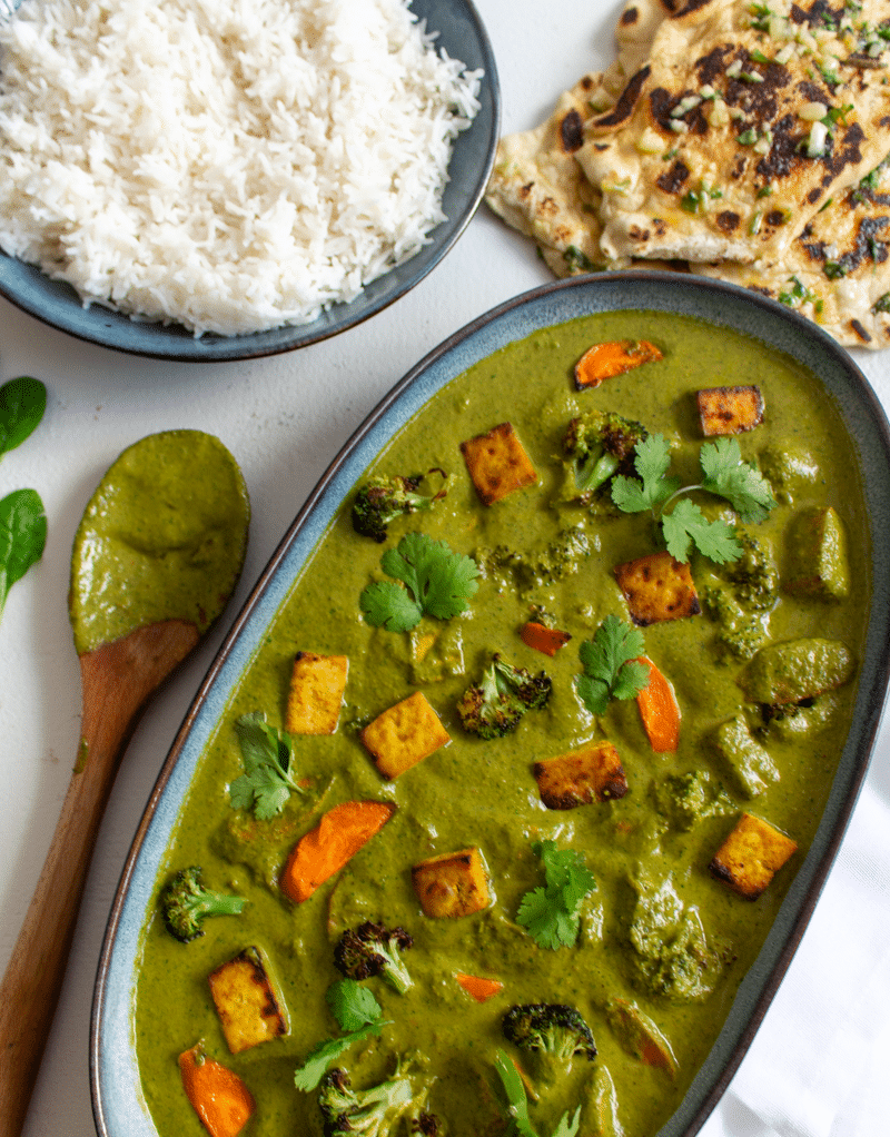 This is the best vegan palak paneer recipe ever! Curried tofu and roasted vegetables come together in a sauce of pureéd garlic, chillies, ginger, spices, and wilted spinach to create a vegan spin on an Indian classic. Healthy, spicy, creamy, and insanely delicious, you're going to love this dish.