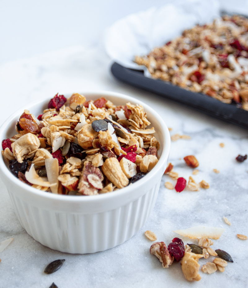 It's healthy and easy granola recipe, loaded with oats, nuts, seeds, fruit, and coated in maple, vanilla, cinnamon, and coconut oil. Crunchy, chewy, sweet, salty, and so addictive, you're going to love this breakfast treat!