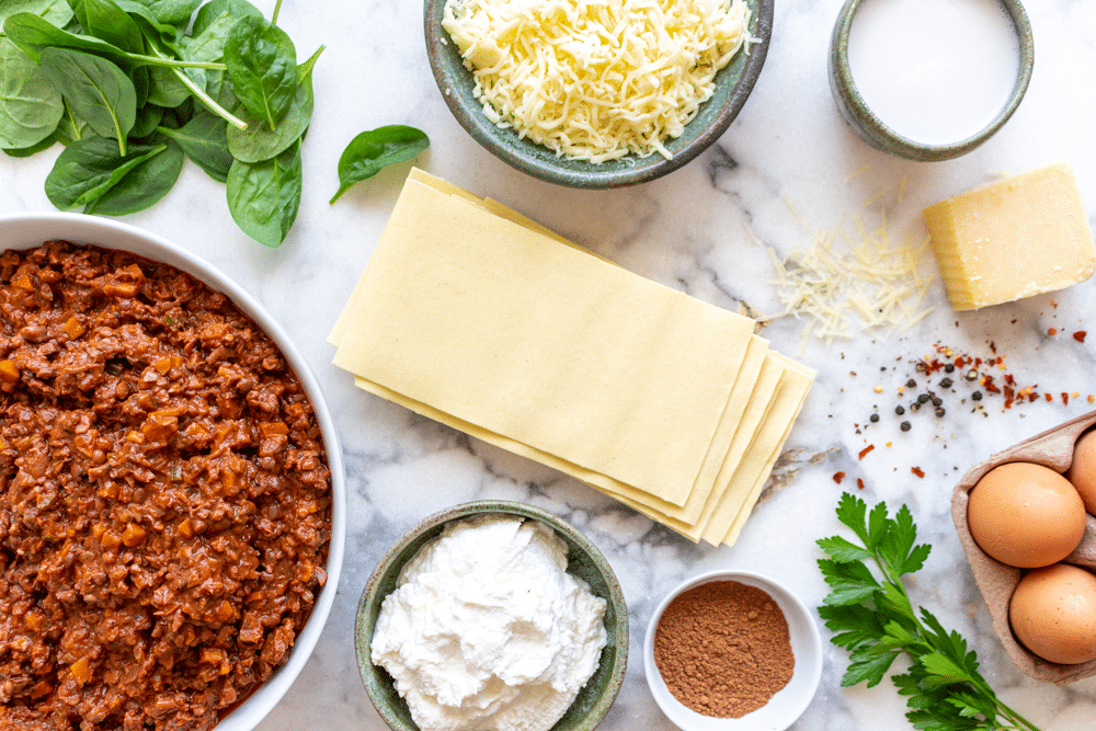 The ingredients to make the best vegetarian lasagna bolognese include a pot of vegan bolognese sauce, pasta sheets, ricotta cheese, spinach, mozzarella cheese, and more.