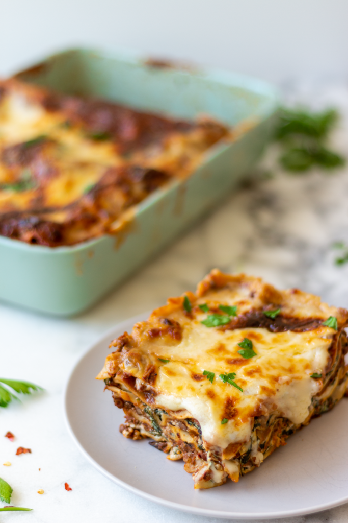 The best vegetarian lasagna recipe, layered with vegan bolognese sauce (with mushrooms, lentils & walnuts), spinach-ricotta, mozzarella, and béchamel sauce!