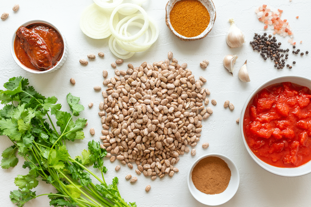 Ingredients for Mexican pinto beans from scratch include pinto beans, tomato, cilantro, chipotle, and spices.
