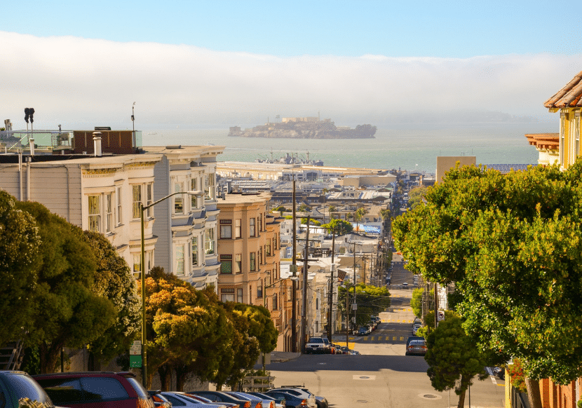 hilly San Francisco street with Alcatraz in the background. A must visit city for your California Bucket List.