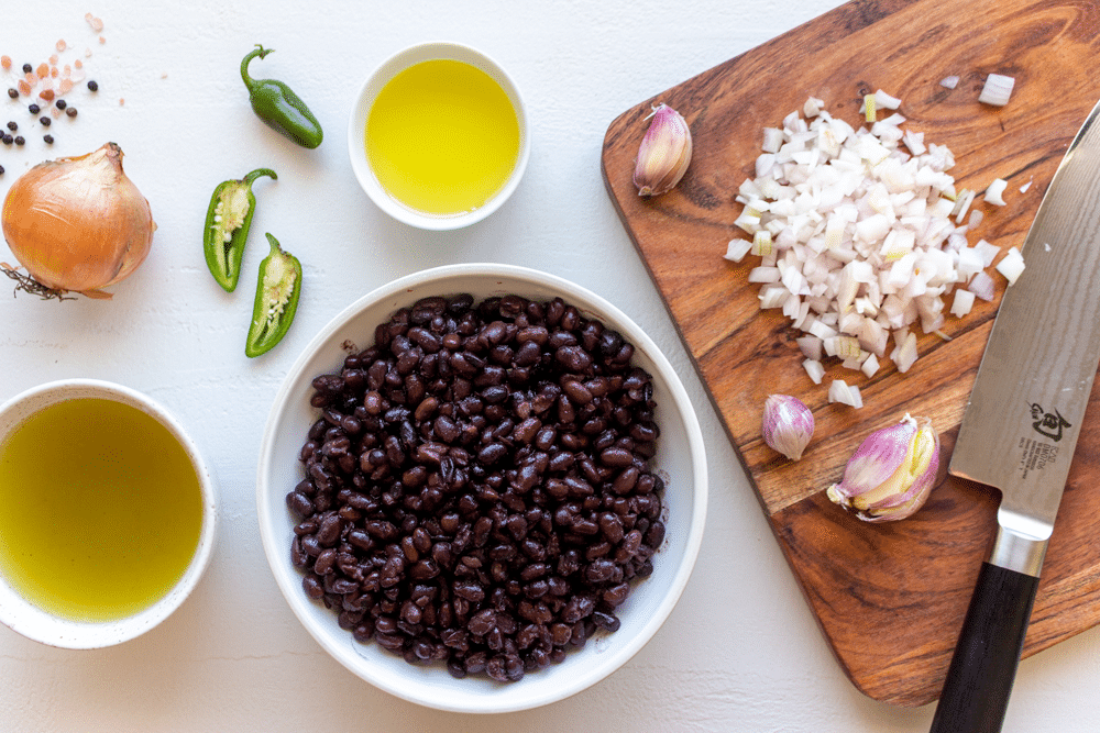 To make these easy refried black beans, you only need a few ingredients. They include canned black beans, olive oil or butter, jalapeño, onion, garlic, salt, and pepper.