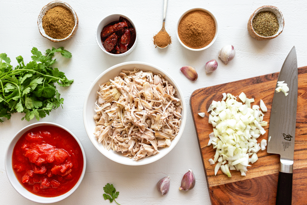 Ingredients for vegan jackfruit tinga include chipotle, tomatoes, garlic, adobo sauce, spices, and more.