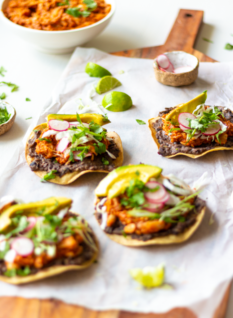 Jackfruit Tostadas make for an easy and delicious Mexican-inspired dinner! These tostadas are crispy, slathered with flavor-packed refried black beans, then topped with smoky, meaty pulled jackfruit. Quick, healthy, and flavor-packed, you'll love this Vegan Jackfruit Tinga in tostadas, tacos, and burritos!