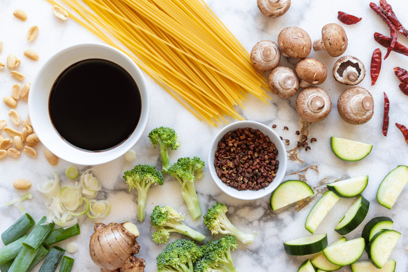 The ingredients for Kung Pao Noodles, including Chinese black vinegar, dark and light soy sauce, Shaoxing cooking wine, mushrooms, dried red chilis, green onions, ginger, noodles, peanuts, and Sichuan peppercorns.