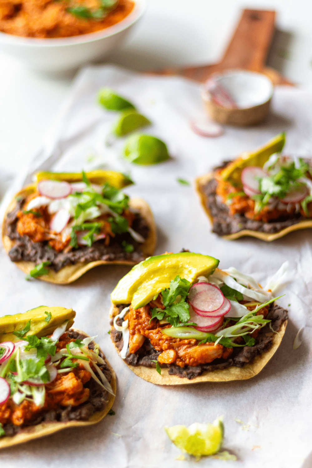 Jackfruit Tinga Tostadas make for an easy and delicious Mexican-inspired dinner! These tostadas are crispy, slathered with flavor-packed refried black beans, then topped with smoky, meaty pulled jackfruit. Quick, healthy, and flavor-packed, you'll love this Vegan Jackfruit Tinga in tostadas, tacos, and burritos!