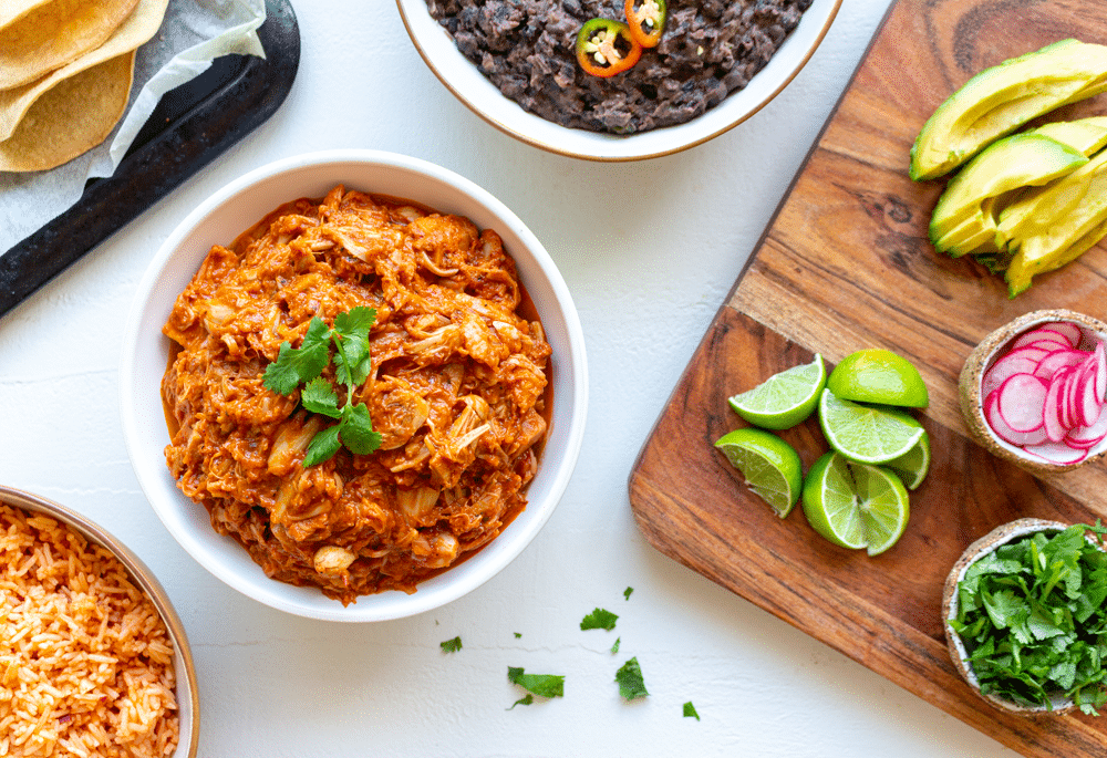 Vegan jackfruit tinga and other Mexican sides like refried black beans and Spanish rice