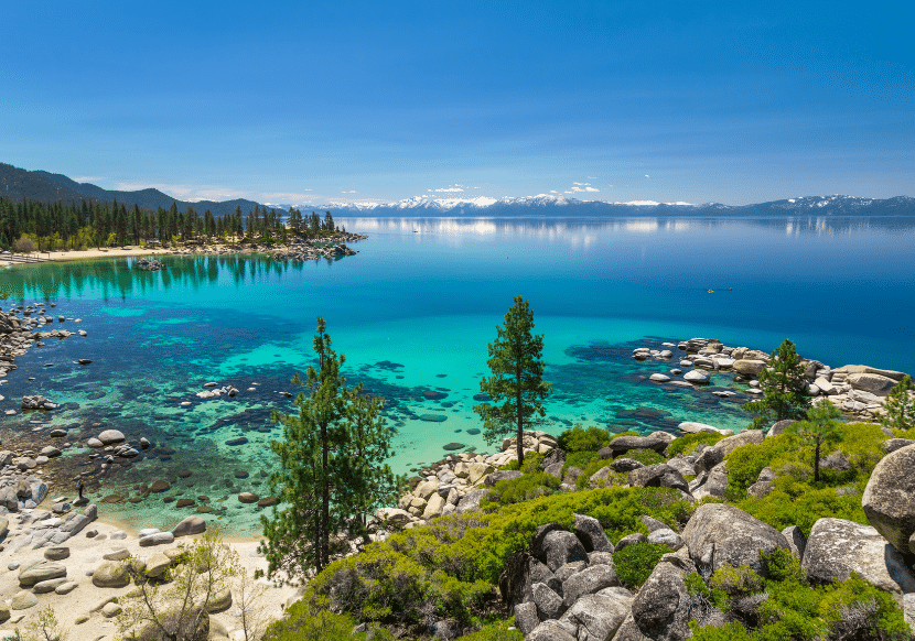 beautiful clear water, rocks, and trees surrounding Lake Tahoe with mountains in the distance. a must-visit destination in california.