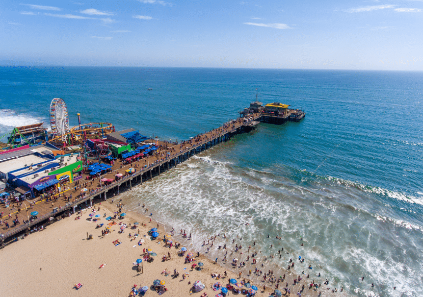 busy pier in Santa Monica with iconic ferris wheel and amusement park over the shoreline