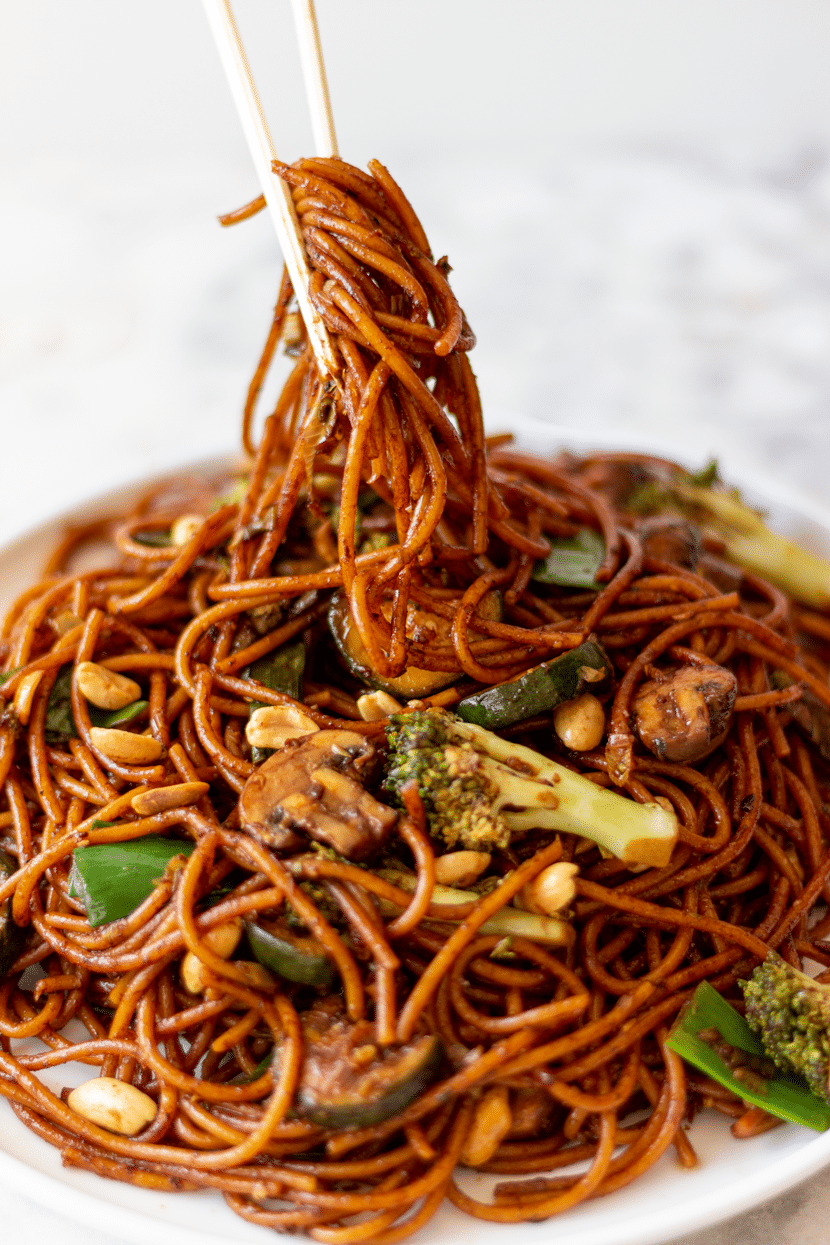 Eating spicy vegan Kung Pao Noodles with Veggies with chopsticks. These noodles are packed with mushrooms, zucchini, broccoli, crunchy peanuts, and the typical ingredients of Chinese stir-fries: black vinegar, shoaxing wine, dark soy, and light soy. And of course, Sichuan peppercorns.