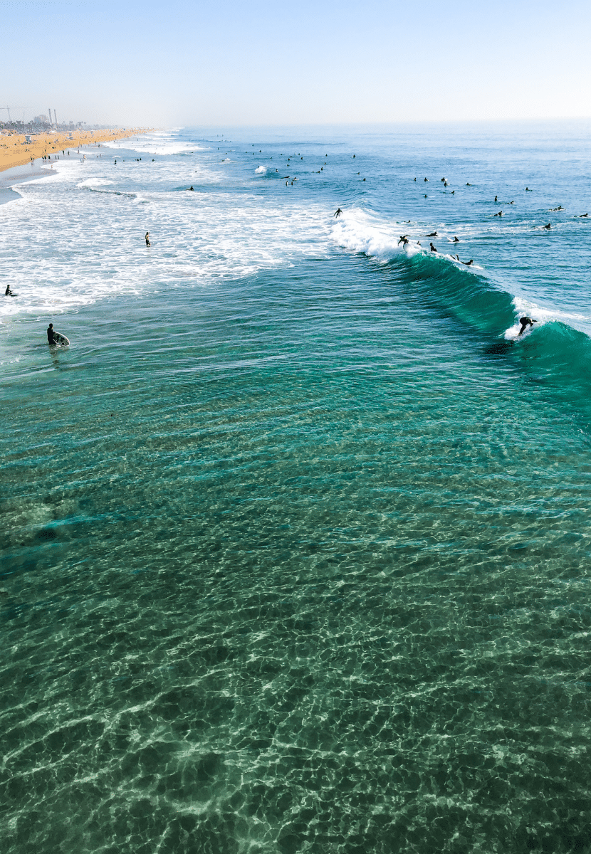 surfers riding waves in Huntington Beach, California, AKA Surf City. Learning to surf is a must on your California bucket list!
