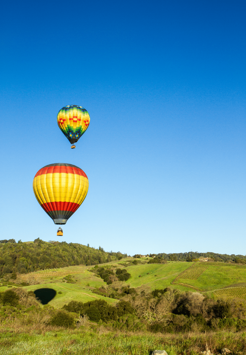 hot air balloons flying over rolling hills and vineyards in Napa Valley. Hot air ballooning is a must on your California bucket list!