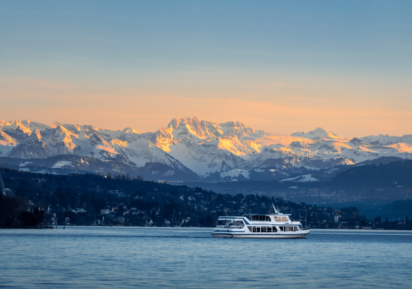 Snow-capped mountains and orange skies, and a boat, at Lake Zurich