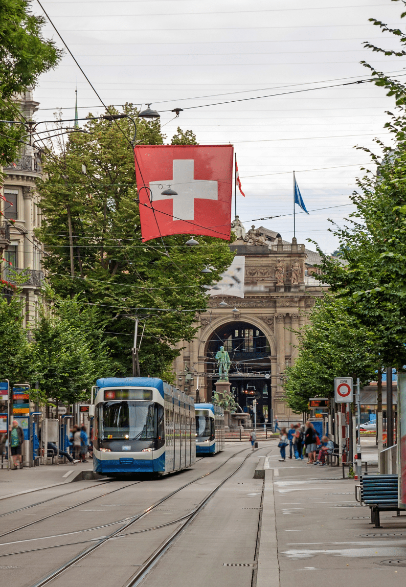 Swiss flag and trams on a busy street in Zurich
