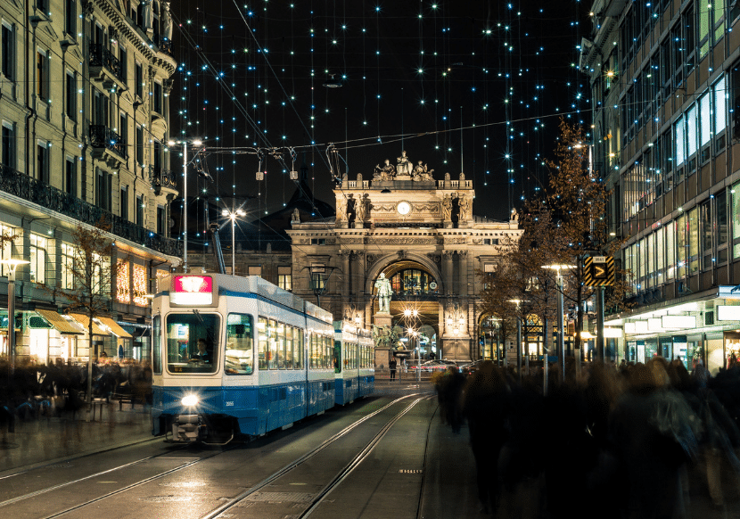 Zurich at night with fairy lights, lots of people, and a tram