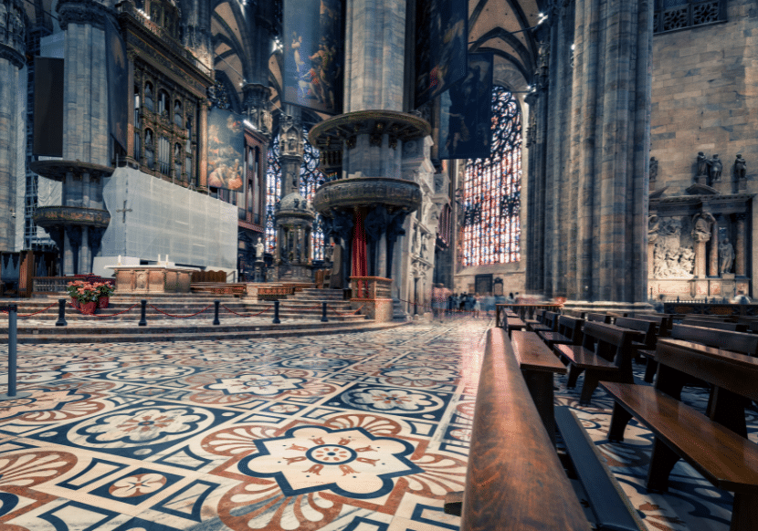 The inside of the Milan Duomo with intricate tile floors and stained glass windows.